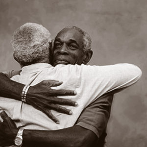 Two men embracing, the individual facing us is looking off to the left and smiling